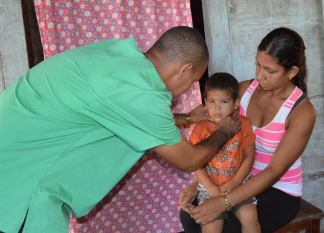 El médico Adrián Alcolea atiende al niño Yurisnel Verdecia, en su casa./Foto: Lino Valerino.