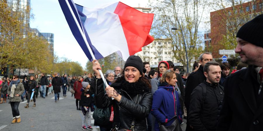 A woman waves a French flag as people take part in a silent walk to s
