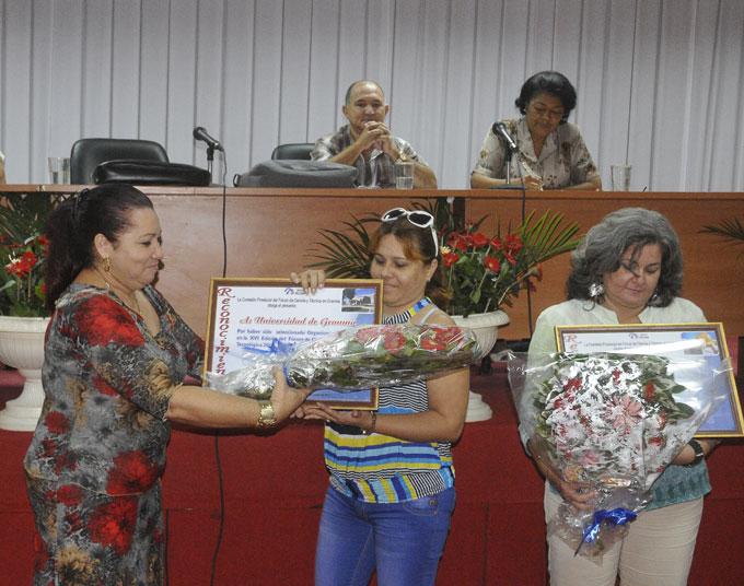 De izquierda a derecha, Teresa Aleaga entrega reconocimiento a la Universidad de Granma y a la Construcción./FOTO Luis Carlos Palacios Leyva