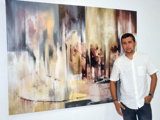 El pintor Raylven Friman junto a una de sus obras. Foto Luis Carlos Palacios
