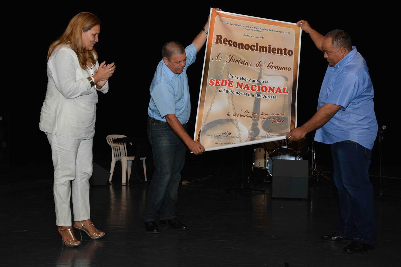 Federico Hernández (D), primer secretario del Comité Provincial del Partido Comunista de Cuba (PCC), y Francisco Escribano Cruz (C), vicepresidente de la Asamblea Provincial del Poder Popular, entregan un reconocimiento a los juristas granmenses, en manos de Yenisey González Rodríguez (I), presidenta de la junta directiva provincial de la Unión de Juristas de Cuba, en el acto nacional por el día del trabajador jurídico, en la ciudad de Bayamo, en Cuba, el 8 de junio de 2016