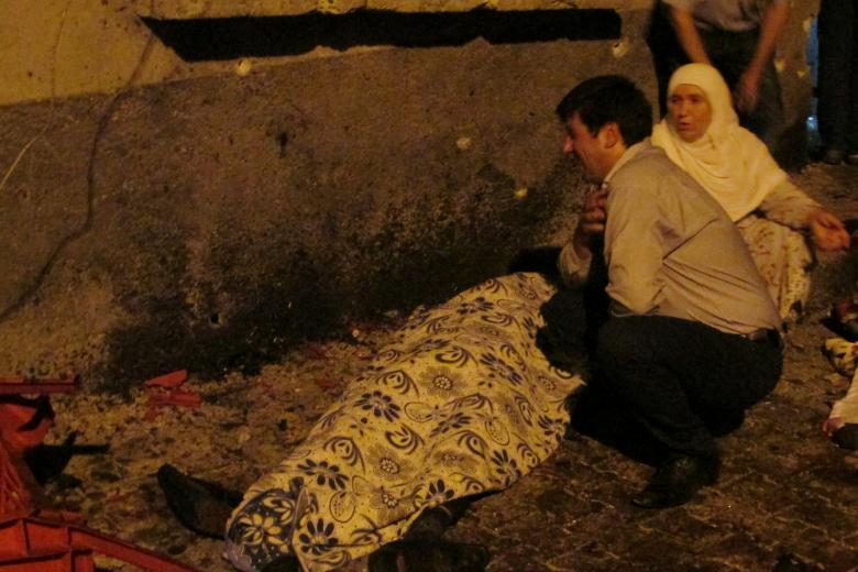 A man and a woman mourn next to a body of one the victims of a blast targeting a wedding ceremony in the southern Turkish city of Gaziantep