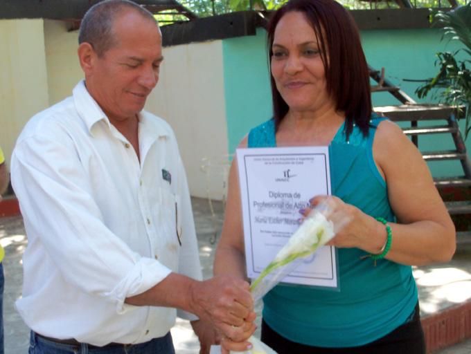Luis René Weeden, funcionario del Comité provincial del Partido Comunista de Cuba en Granma, entrega el certificado a María Esther Marange Duarte, de la sociedad de las geocienciasFOTO/Orlando Fombellida Claro