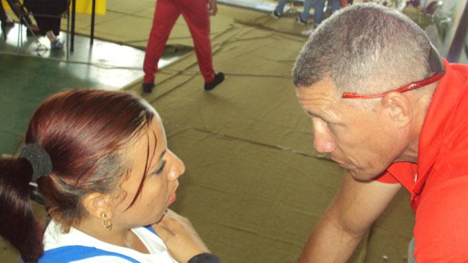 El entrenador Ramón Martínez alienta a su pupila Leydis antes de subir al banco de fuerza