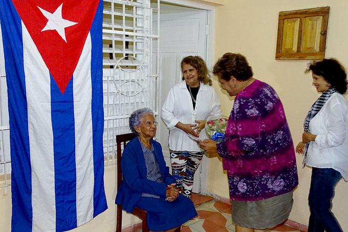Olga Lidia Tapia Iglesias entrega un ramo de flores a Amada Santos Hernández, madre de Carlos Martí Santos, director del equipo Cuba de béisbol / Fotos Luis Carlos Palacios Leyva